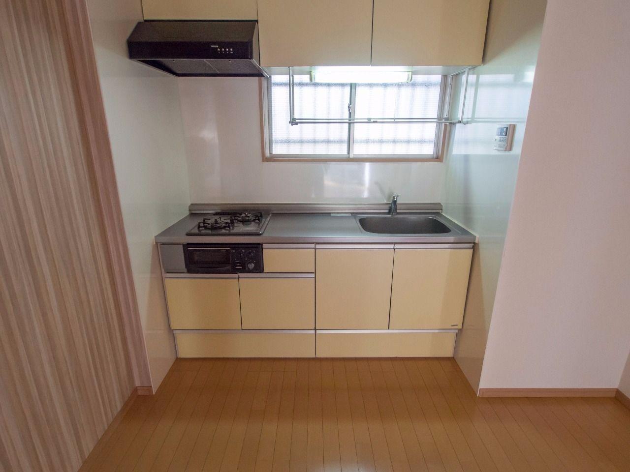 落ち着いた色味のキッチンには換気できる窓付き
